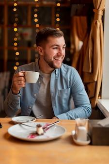 Szczęśliwy człowiek pije kawę w restauracji