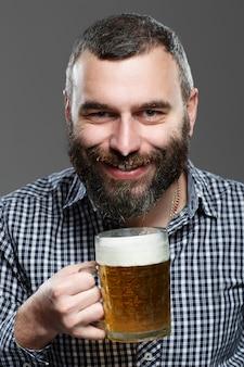 Szczęśliwy człowiek pije piwo z kubka