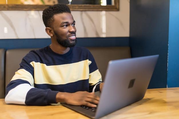 Szczęśliwy człowiek pisze tekst na laptopie w nowoczesnej kawiarni. szczęśliwy student afryki surfowania po internecie na laptopie