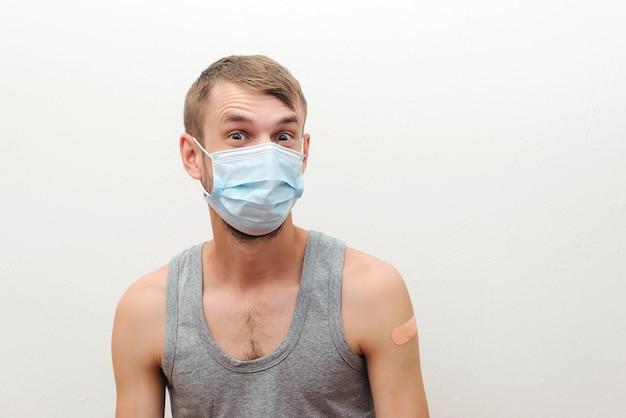 Szczęśliwy człowiek pokazując ramię z bandażem po otrzymaniu szczepionki. szczepienia, immunizacja, inokulacja i pandemia koronawirusa. człowiek dostaje szczepienie na krukowicę. osoba nosząca maskę.