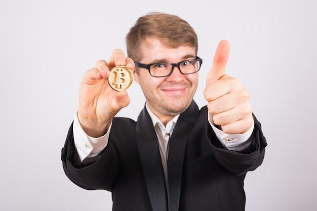 Szczęśliwy człowiek posiadający duże bitcoiny i pokazując kciuki do góry