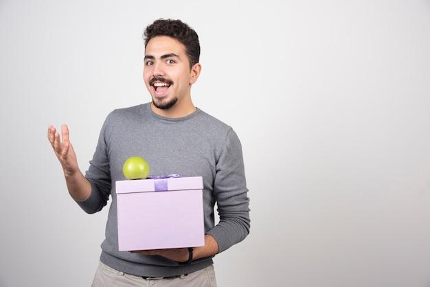 Szczęśliwy człowiek posiadający fioletowe pudełko z zielonym jabłkiem.