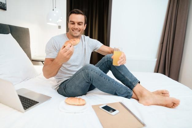 Szczęśliwy człowiek pracuje i śniadanie w łóżku.