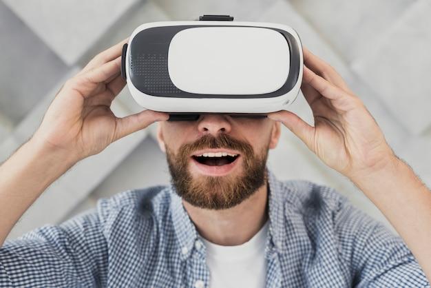 Szczęśliwy człowiek próbuje wirtualnego zestawu słuchawkowego