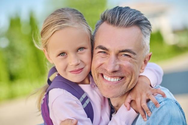 Szczęśliwy człowiek przyczajony przytulający swoją uroczą córkę