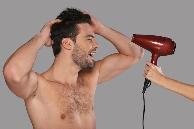 Szczęśliwy człowiek. przystojny młody mężczyzna suszy włosy i uśmiecha się stojąc na szarym tle