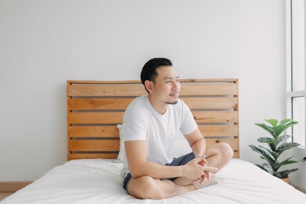 Szczęśliwy człowiek relaksujący się i relaksujący na swoim łóżku