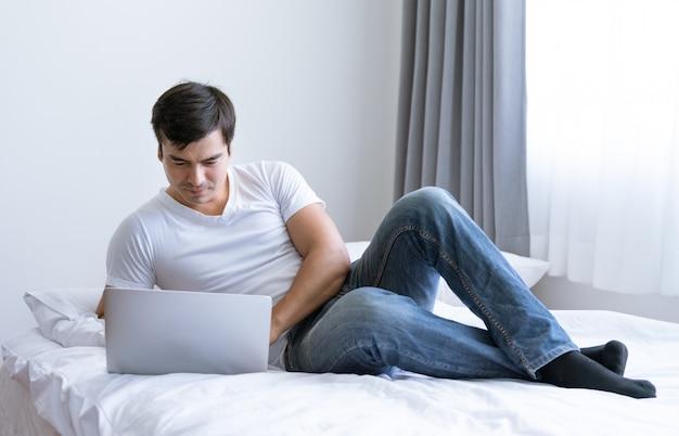 Szczęśliwy człowiek relex za pomocą laptopa na łóżku w sypialni