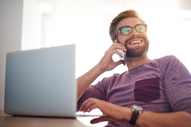 Szczęśliwy człowiek robi biznesowi w domowym biurze