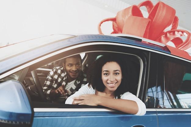 Szczęśliwy człowiek robi prezent dla kobiety kupując samochód marzeń.