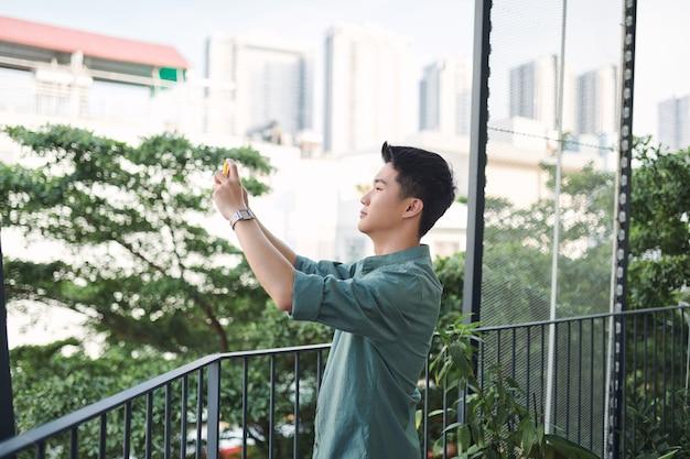 Szczęśliwy człowiek robi zdjęcia telefonem komórkowym stojącym na zewnątrz na balkonie