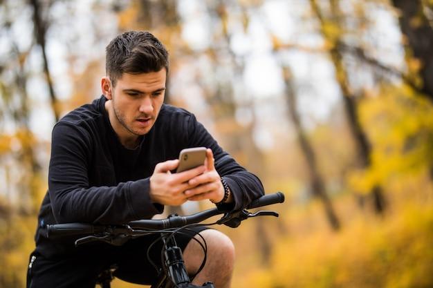 Szczęśliwy człowiek rowerzysta jeździ w słonecznym lesie na rowerze górskim. przygodowa wycieczka.
