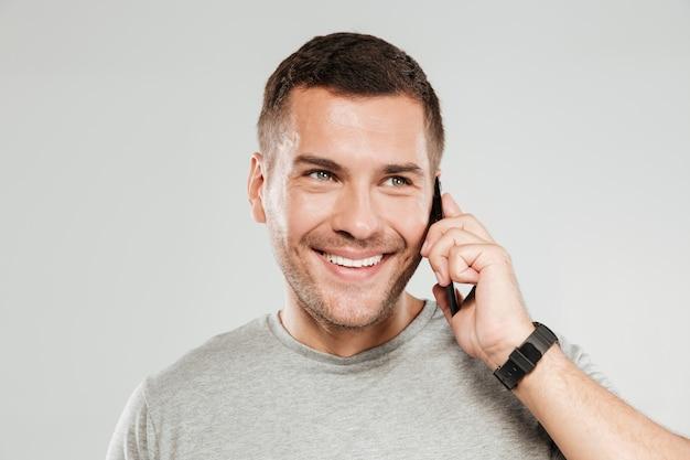 Szczęśliwy człowiek rozmawia przez telefon komórkowy.