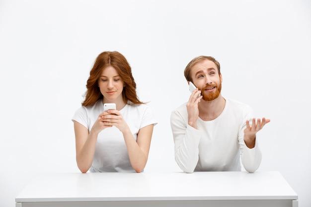 Szczęśliwy człowiek rozmawiać przez telefon, ruda dziewczyna grać w gry