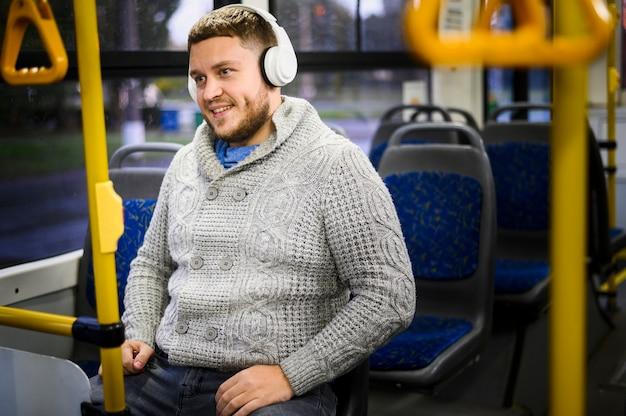 Szczęśliwy człowiek siedzi na autobusowym siedzeniu z hełmofonami