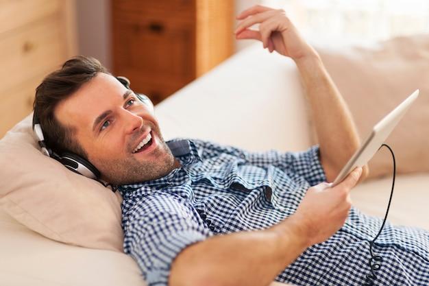 Szczęśliwy człowiek słuchanie muzyki i leżenie na kanapie