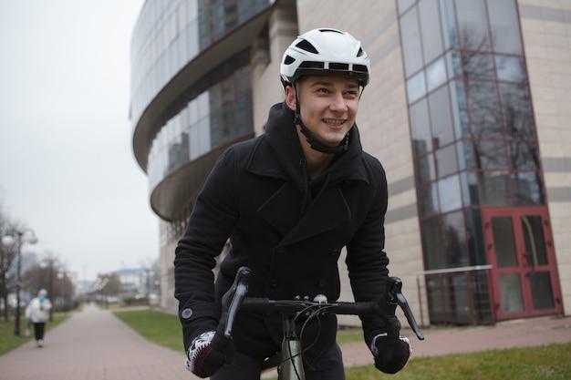 Szczęśliwy człowiek śmiejący się, cieszący się jazdą na rowerze po mieście jesienią lub zimą