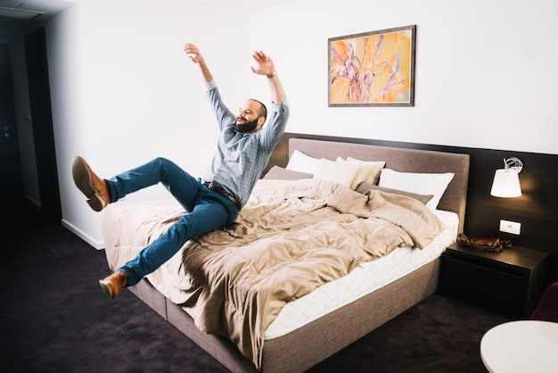 Szczęśliwy człowiek spada na łóżku