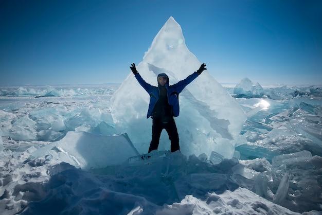 Szczęśliwy człowiek stoi na lodzie zimą na tle błękitnego nieba
