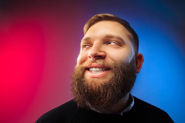 Szczęśliwy człowiek stojący i uśmiechnięty na białym tle na różowym studio