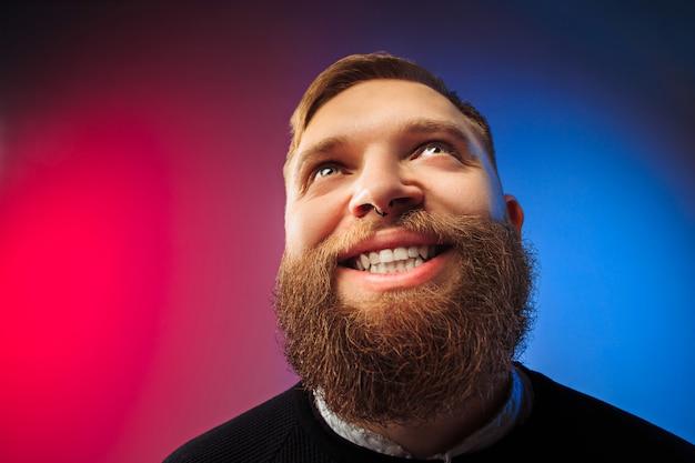 Szczęśliwy człowiek stojący i uśmiechnięty przed różową ścianą.
