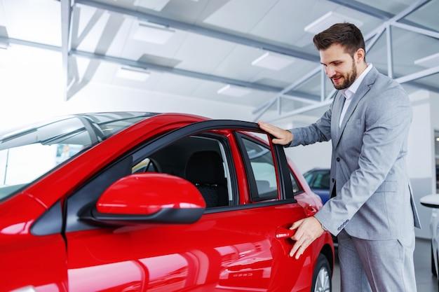 Szczęśliwy człowiek stojący obok zupełnie nowego samochodu w salonie samochodowym i otwierając drzwi.