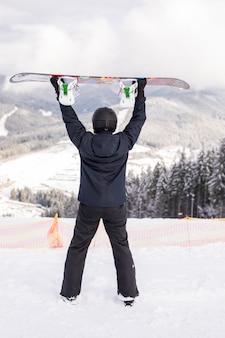 Szczęśliwy człowiek stojący z snowboard nad głową na szczycie wzgórza gór