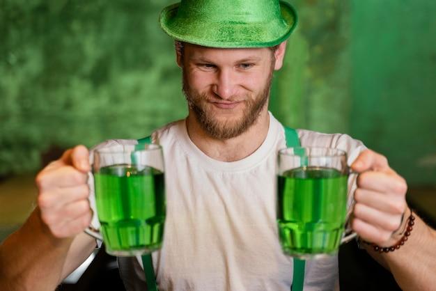 Szczęśliwy człowiek świętuje św. patrick's day z napojami