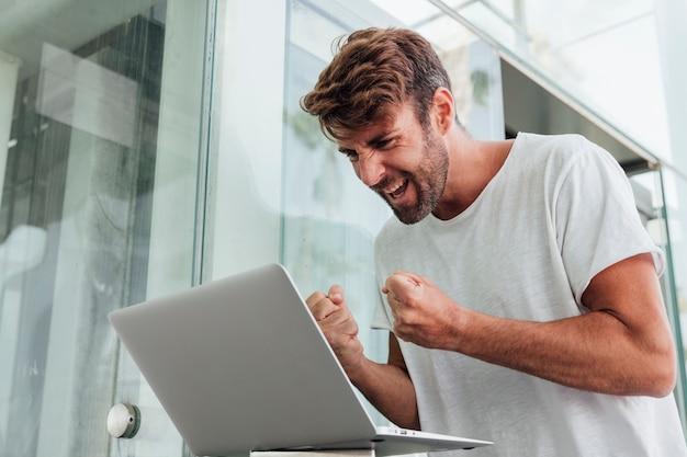 Szczęśliwy człowiek świętuje z notebooka