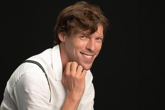 Szczęśliwy człowiek toothy uśmiecha się dotykając jego brodę ręką, patrząc na kamery. młody uśmiechnięty przystojny na sobie białą koszulę na białym tle na czarnej ścianie.