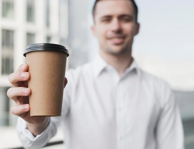 Szczęśliwy człowiek trzyma filiżankę kawy