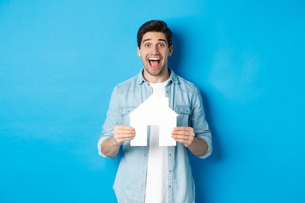 Szczęśliwy człowiek trzyma model domu i uśmiecha się podekscytowany, kupuje nieruchomość lub wynajmuje mieszkanie, stojąc przed niebieską ścianą
