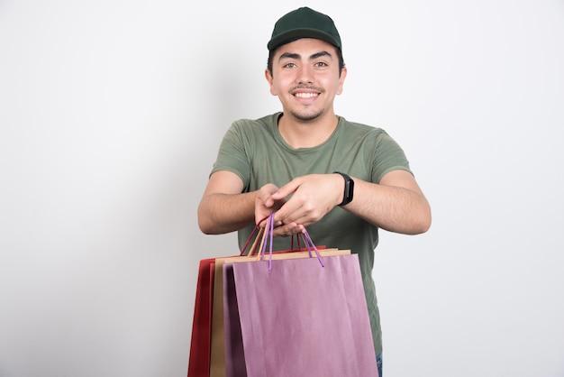 Szczęśliwy człowiek trzyma torby na zakupy na białym tle.