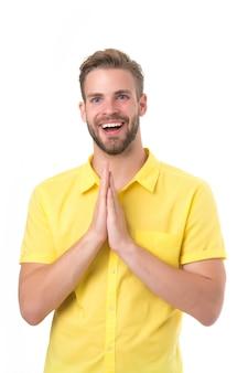 Szczęśliwy człowiek trzymać ręce splecione na białym tle. facet z uśmiechem na brodatej twarzy. bądź pozytywnie nastawiony. czuć się podekscytowanym. pozytywne emocje. modląc się o coś. na co dzień w swoim stylu.
