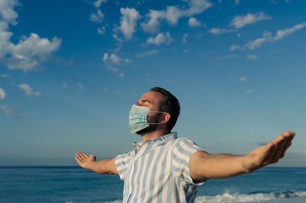 Szczęśliwy człowiek ubrany w maskę medyczną na zewnątrz na tle błękitnego nieba. osoba korzystająca z morza w lecie.