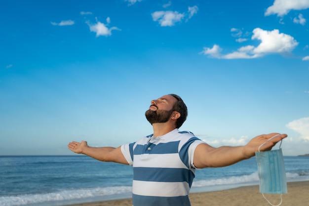 Szczęśliwy człowiek ubrany w maskę medyczną na zewnątrz na tle błękitnego nieba