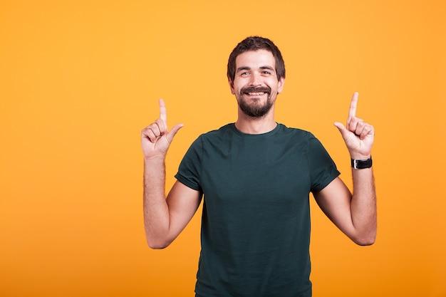 Szczęśliwy człowiek uśmiecha się i wskazuje palcami. copyspace dostępne dla twojej promocji tekstowej i reklamowej. strzał na pomarańczowym tle