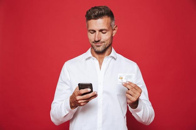 Szczęśliwy człowiek w białej koszuli trzymający kartę kredytową i smartfona na czerwono