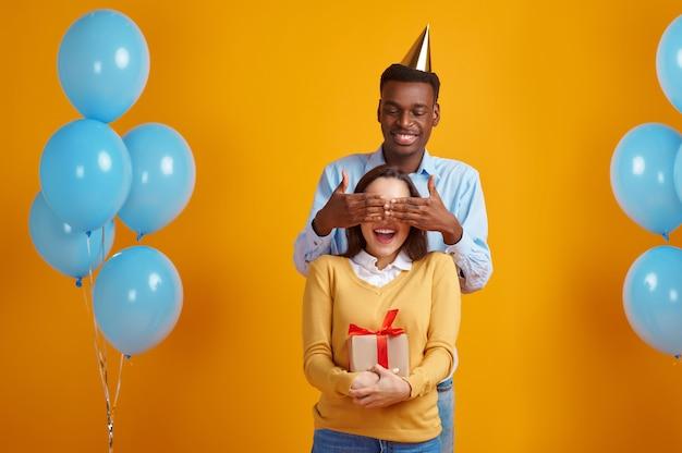 Szczęśliwy człowiek w czapce gratuluje swojej kobiecie z pudełkiem na prezent, żółtym tle. całkiem miłosna para, impreza lub urodziny, dekoracja balonów