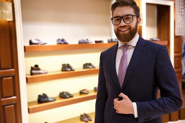 Szczęśliwy człowiek w garniturze i okularach stading w pobliżu półki