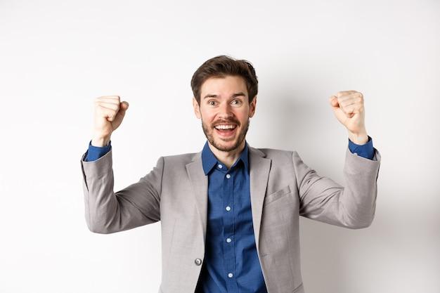 Szczęśliwy człowiek w garniturze podnosząc ręce do góry i śpiewając, oglądając mecz sportowy, wygrywając w kasynie i świętując, stojący podekscytowany na białym tle.