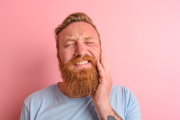 Szczęśliwy człowiek w jasnoniebieskiej koszulce ma ból w zębach