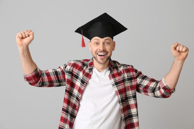 Szczęśliwy człowiek w kapeluszu dyplomowym na szarym