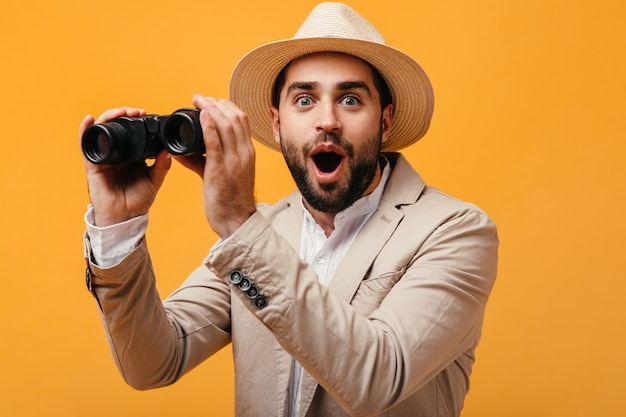 Szczęśliwy człowiek w kapeluszu i beżowym garniturze, trzymający lornetkę