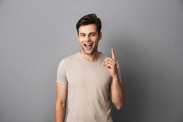 Szczęśliwy człowiek w koszulce pokazuje palec z szczęśliwym uśmiechem