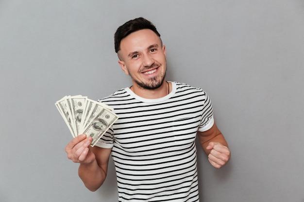 Szczęśliwy człowiek w koszulce, trzymając pieniądze i patrząc na kamery