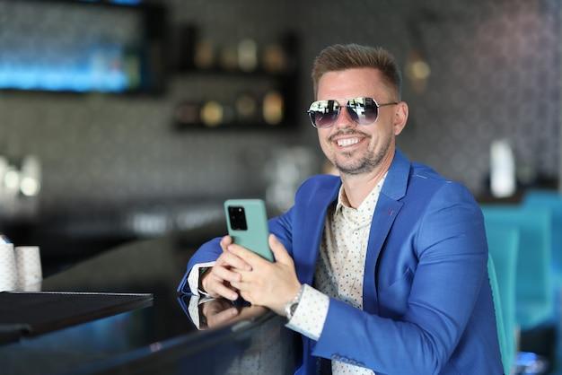 Szczęśliwy człowiek w niebieskiej kurtce z brodą i okularami przeciwsłonecznymi siedzi przy barze i czeka.
