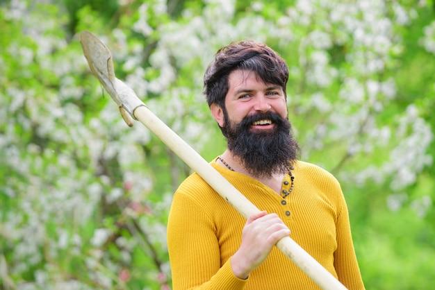 Szczęśliwy człowiek w ogrodzie wiosną. ogrodnik w gospodarstwie ekologicznym z narzędziami ogrodniczymi do sadzenia łopatą.