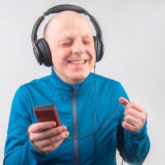 Szczęśliwy człowiek w pełnowymiarowych przenośnych słuchawkach słucha muzyki za pomocą odtwarzacza cyfrowego.