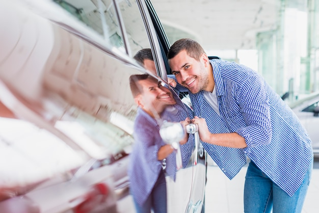 Szczęśliwy człowiek w salonie samochodowym